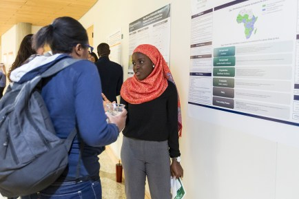 student presents research poster