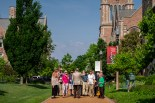 Group of people standing while listening to tour guide speak on WashU campus.