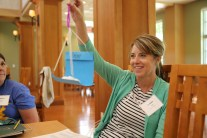 Teacher proudly holds up a paper creation made at the conference.