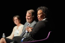 Three people sit on a stage as part of a panel discussion.