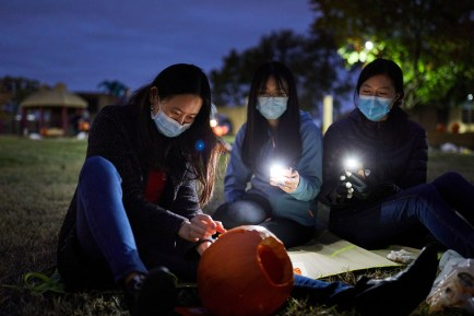 Medical students, including Rohana Gao (left), Amanda Li and Rebecca Lin, gather outside Oct. 24 at Hudlin Park to carve pumpkins while wearing masks during the COVID-19 pandemic. (Photo: Matt Miller/School of Medicine)
