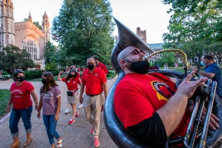 The Red & Black Brass Band lead the Martin family and others to a welcome event on Mudd Field Aug. 21. (Photo: Joe Angeles/Washington University)