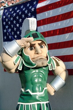 Sparty saluting in front of a flag