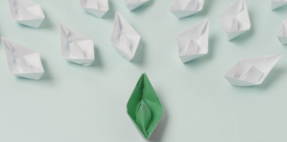 graphic of a paper boat leading others, representing leadership.