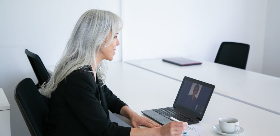 Female office worker talking to colleague via video chat on laptop while sitting at table with cup of coffee and analyzing diagram.