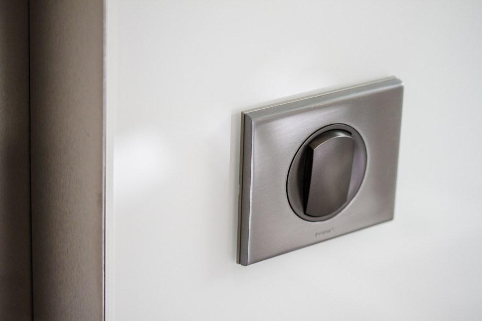 Détail sur interrupteur, paroi verre laqué, cadre acier inoxydable
