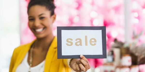 Young woman holding SALE sign in gift shop.  Focus on sign.