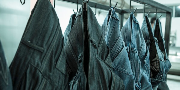 Jeans pants getting spray paints for special effects in denim manufacturing factory.
