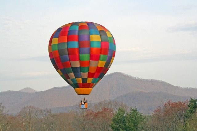 A colorful hot air balloon glides over the Blue Ridge Mountains in the fall