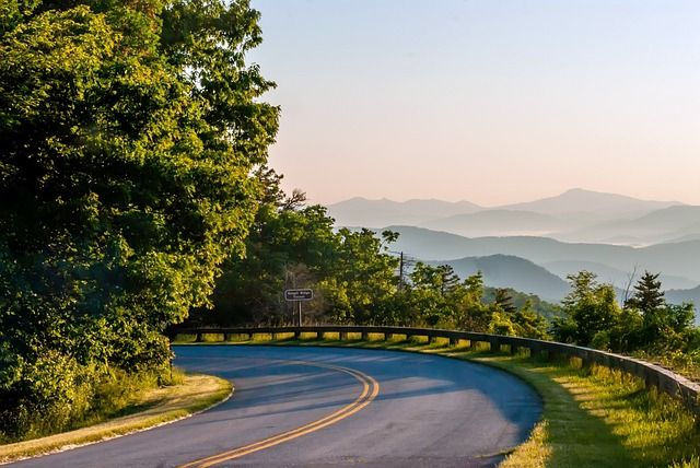 The Blue Ridge Parkway curves around a bend with mountain vista in distance
