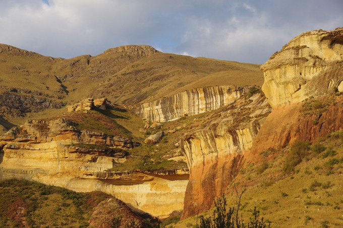 """Late afternoon sun shines off sandstone cliffs in the Golden Gate National Park. In the19th and early 20th centuries blocks of eastern Free State sandstone, prized for their softness and lovely colour, were used to build churches, public buildings and grand homes across the province. <em>(<a href=""""https://www.flickr.com/photos/mr-pi/25833266367/"""" target=""""_blank"""" rel=""""noopener"""">Pieter Edelman</a>, <a href=""""https://creativecommons.org/licenses/by-nc-nd/2.0/"""" target=""""_blank"""" rel=""""noopener"""">CC BY-NC-ND 2.0</a>)</em>"""