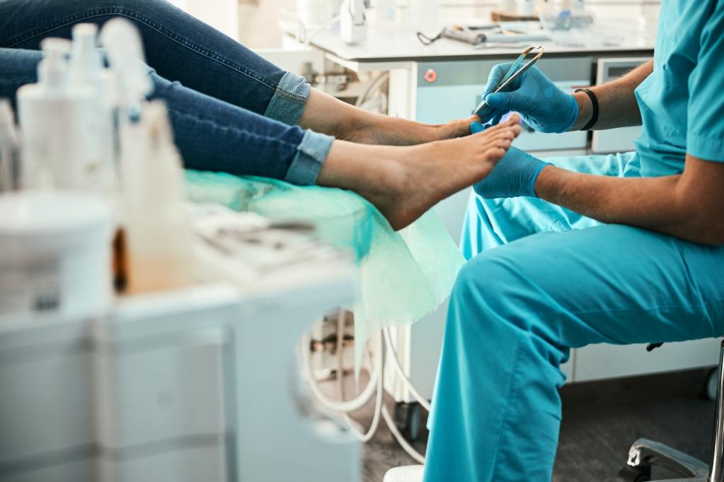 Professional doctor podiatrist doing medical pedicure procedure in the cabinet