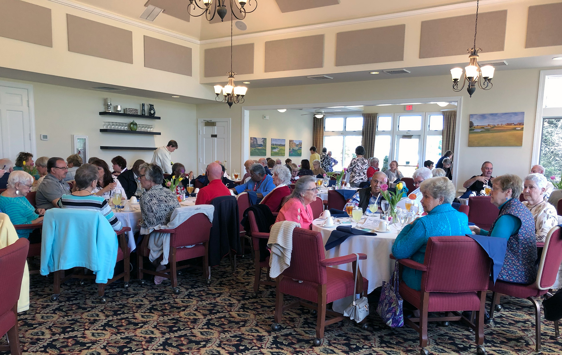 Members gather in the dining room for social hour prior to lunch.