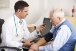 American doctor taking senior man's blood pressure