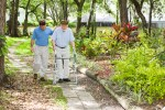 son walking with senior father in park