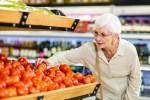 Senior woman choosing her tomatoes in supermarket