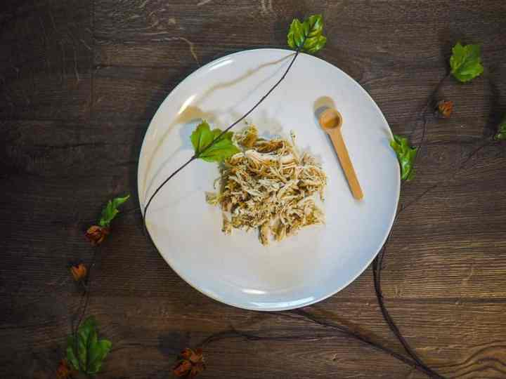 Shredded chicken on a white plate with orange flowers and a small wooden spoon on a gray wood floor.