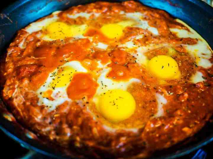 A black frying pan with tomato sauce simmering and 5 eggs.