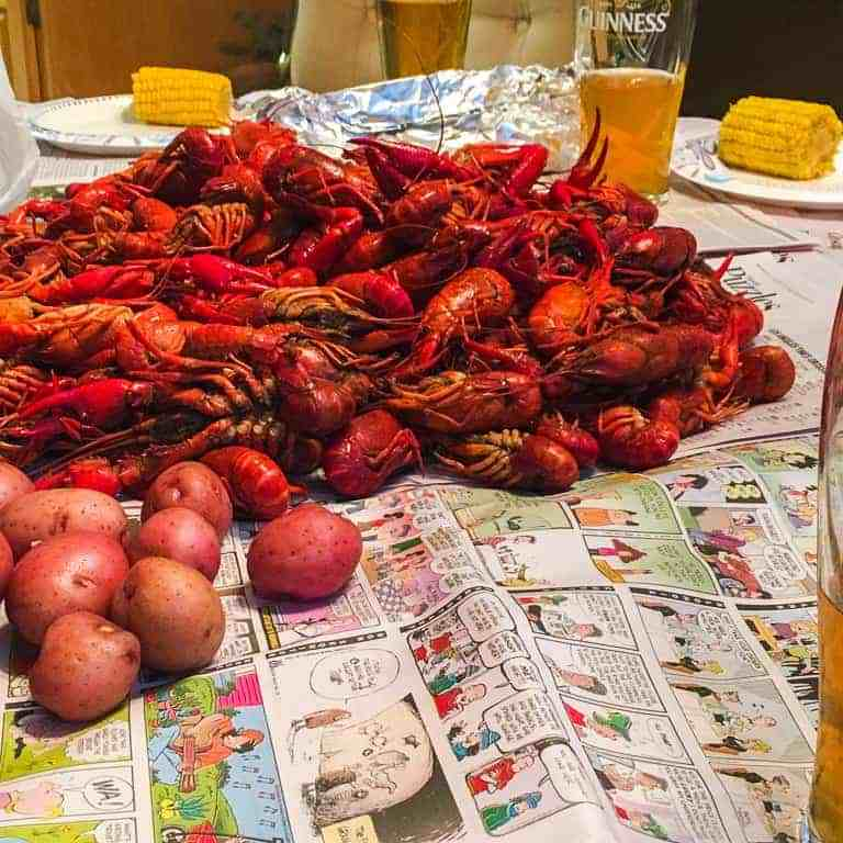 A table covered in newspaper with a pile of crawfish.