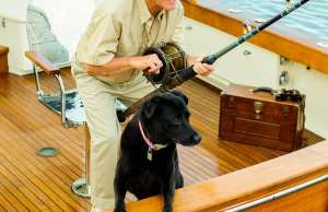 An image of a man and his dog fishing with a fighting chair