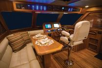Roominess is a priority aboard with generous dimensions afforded at the lower helm—note the hand-crafted wheel—and casual dining area that doubles as a work space. Photo: jlambertphotos.com
