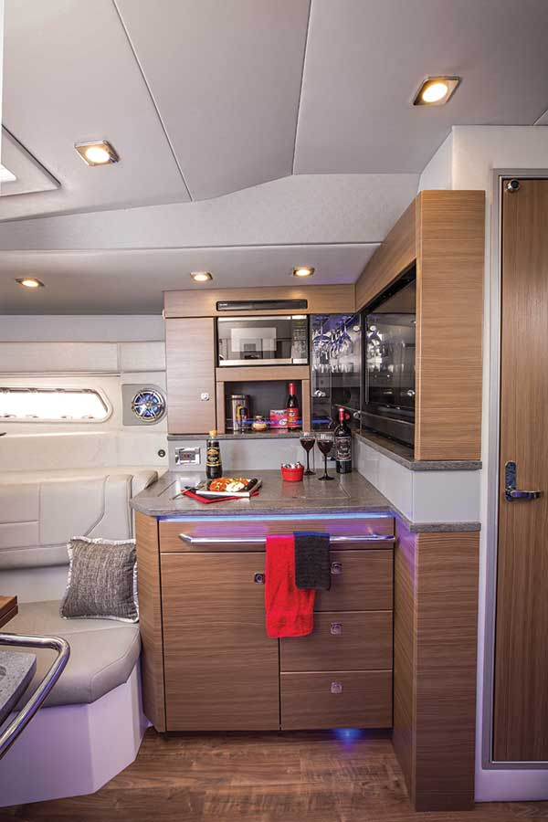 The lower galley is compact yet well-appointed with secure wine glass racks and bottle storage in the blue LED-lighted cabinet.