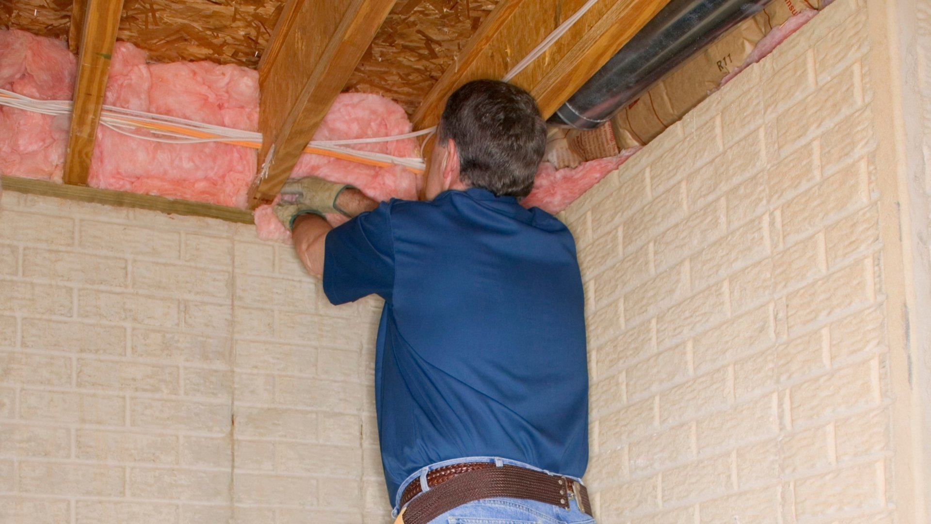 Technician Inspecting Insulation in the Ceiling and Wall