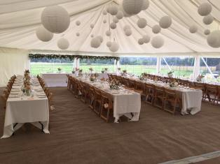 Trestle tables and lots of paper lanterns adorned this traditional style wedding marquee at Hill Place in Swanmore.