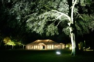 Marquee and trees illuminated against the night sky ...