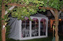 A pretty party tent viewed from the garden vine covered pergola ...
