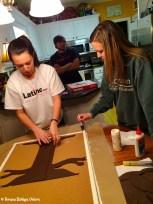 Emily helps Anna Marie glue to felt tree to the bulletin board.