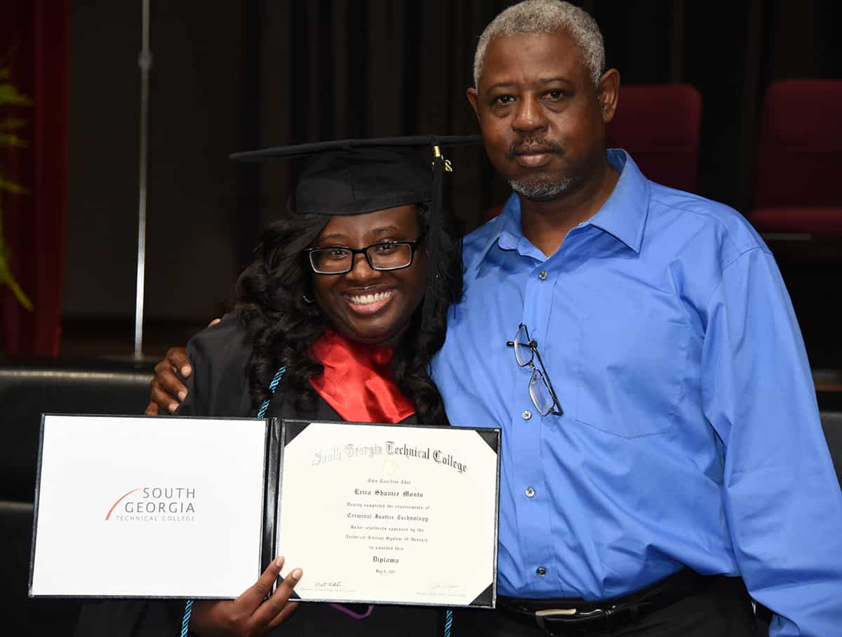 A smiling girl holds her diploma and hugs a man.