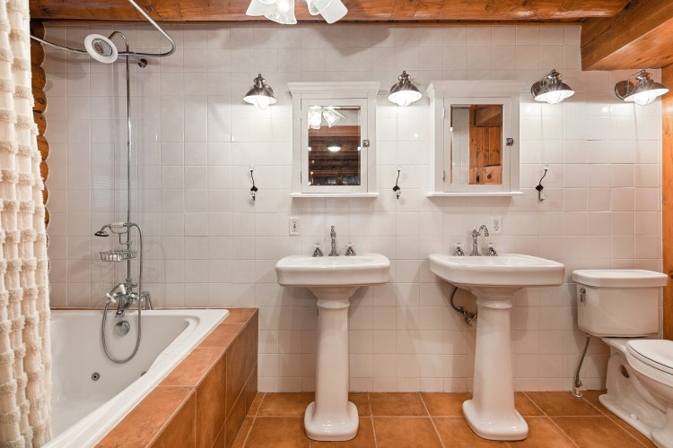 The master bathroom showing two pedestal sinks and whirlpool tub