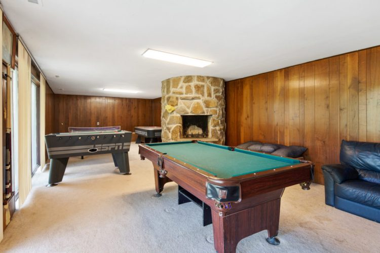 The lower level game room at 15 Springhill Road has a stone fireplace