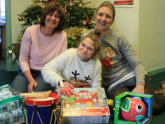 Donors from Shepherd's Friendly Society, with presents they delivered, and Seashell Trust's student Evie Gilbert