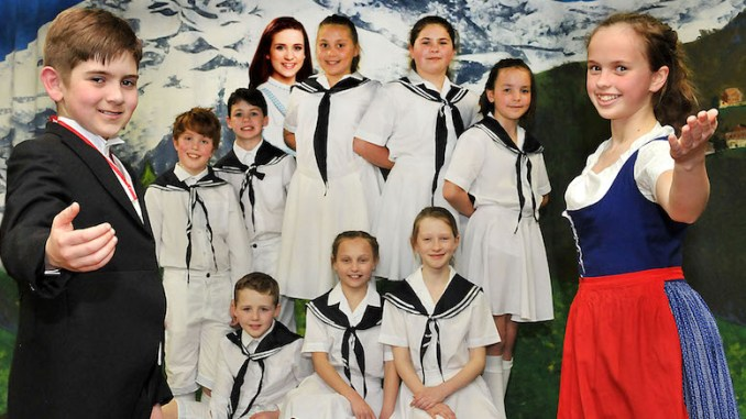 Pictured in front of the Family von Trapp are Dylan Southern as Captain von Trapp and Emily Booker as Maria with Danielle as an insert photo.