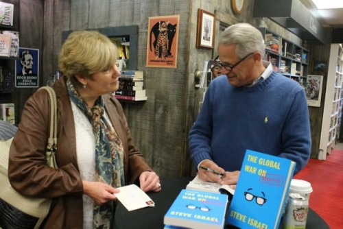 Rep. Steve Israel signs a copy of his book for Debbie O'Kane. Photo: Denise Civiletti