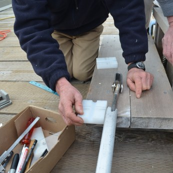 A pulley system at the bottom of the mast when pulled will role the sail up around the foil.