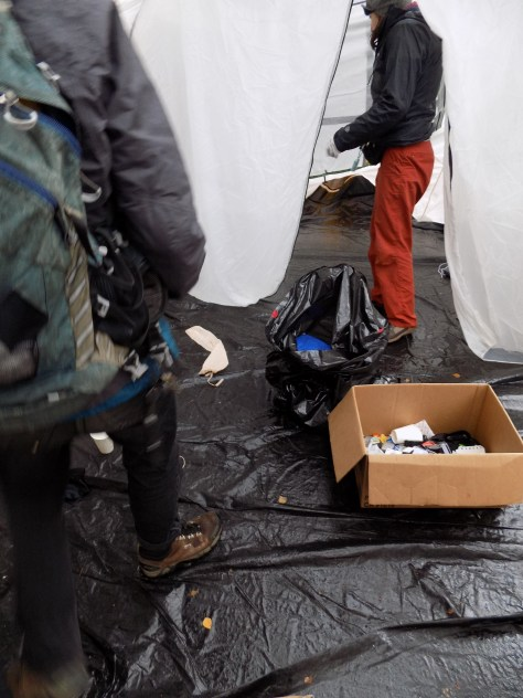 Image 4 Caption--Volunteer medics sweep a tent for used needles while the camp is packed up.