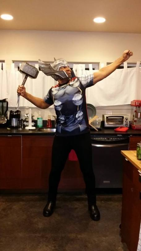 A man of color stands in a home kitchen wearing a Thor outfit, helmet and all, wielding Thor's hammer, his fist aimed toward the sky.