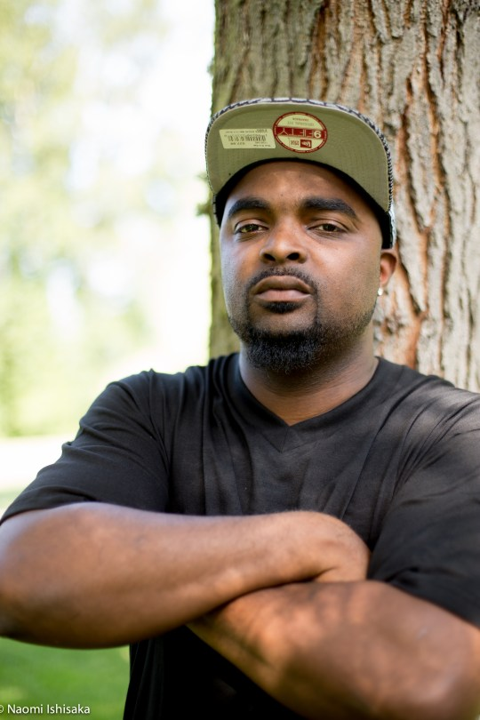 A black man in a black t-shirt leans against a tree, his arms folded, looking into the camera; wearing a baseball cap