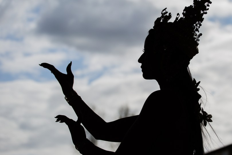 Sillouhette of someone performing a Cambodian moonlight dance in traditional garb (against a backdrop of a cloudy blue sky)