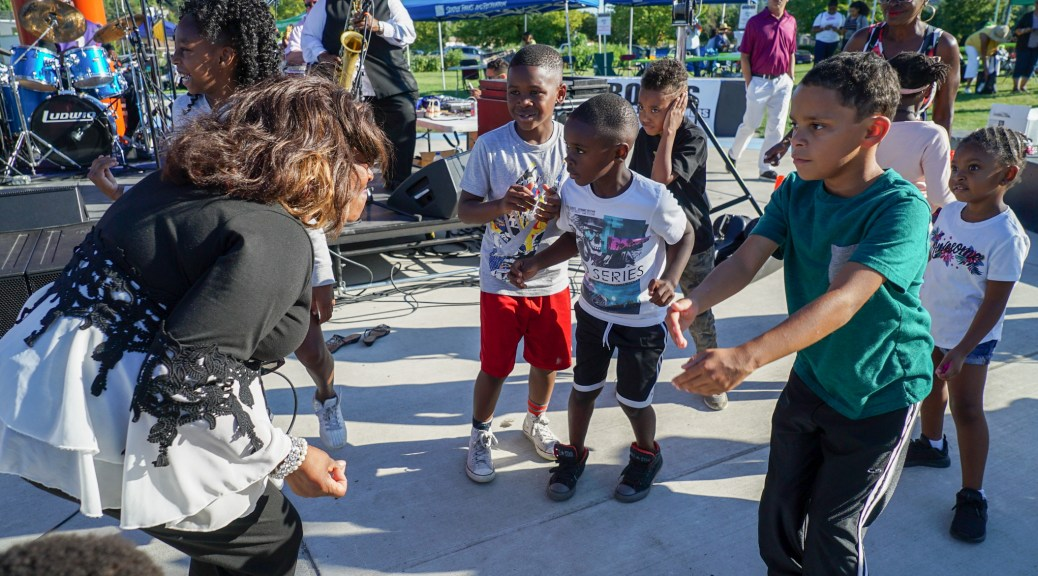 Photo depicting Josephine Howell (left) dancing with children at Jimi Hendrix Park.