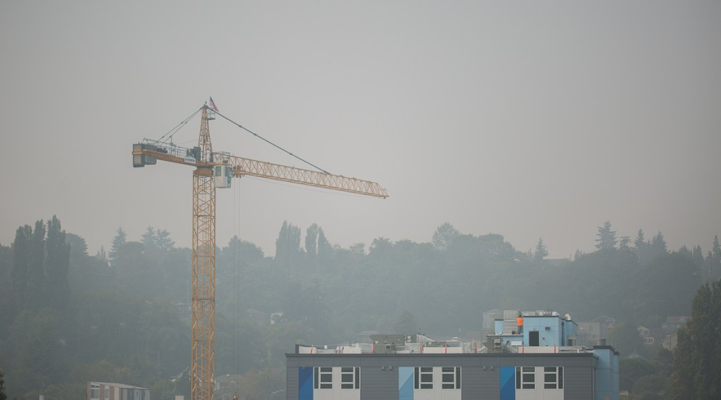 construction worker stands atop building shrouded in wildfiresmoke 2020 — photo by carolyn bick