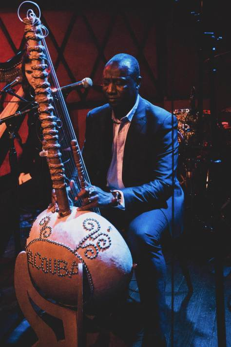 A Black man, Yacouba Sissoko, with very short black hair, wearing a dark suit and with a white shirt under the jacket, plays a tall stringed instrument decorated with beads on a blue-lit stage.