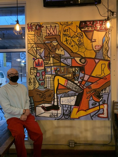 Male-presenting individual sits next to his artwork depicting colorful human figures.