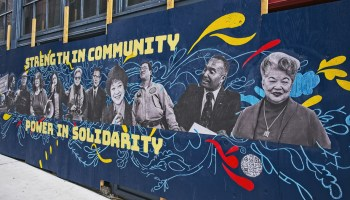 """Blue mural depicting black-and-white photos of Asian-presenting and Black-presenting individuals with yellow words reading """"Strength in community; power in solidarity"""" bordering the mural"""