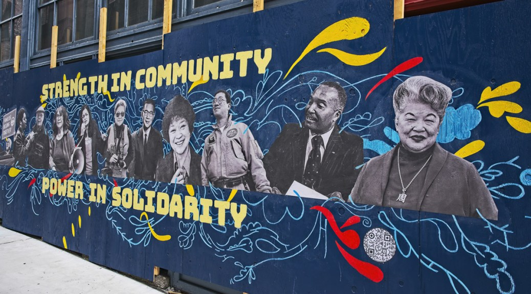 "Blue mural depicting black-and-white photos of Asian-presenting and Black-presenting individuals with yellow words reading ""Strength in community; power in solidarity"" bordering the mural"