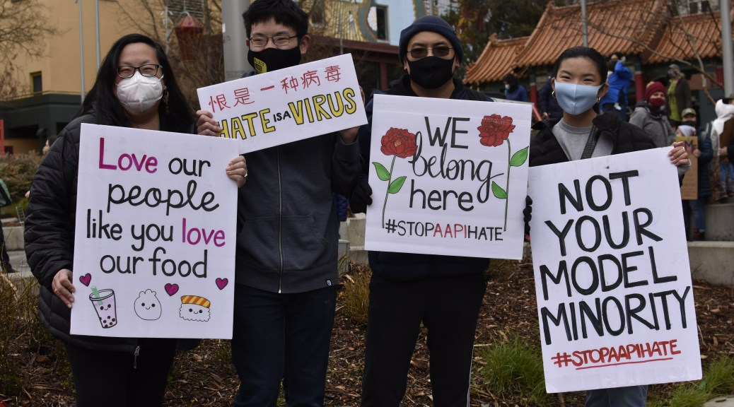Individuals holding signs with various slogans to protest hatred and violence towards AAPI community