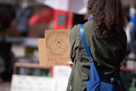 "A person attending the Massage Parlor Outreach Project Vigil, Mon 3/22 holds a cardboard sign with a venn diagram reading ""racism, sexism, colonialism."" (Photo: Chloe Collyer)"